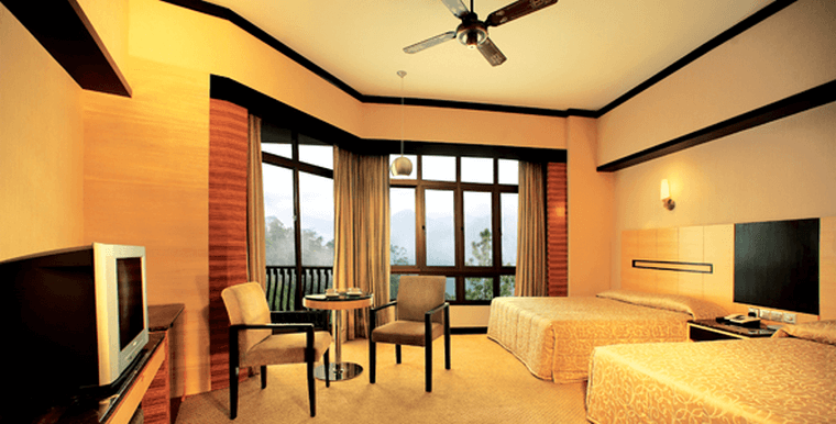 Hotel room interior decorated in beige and dark browns with two queen beds and large windows with scenic view