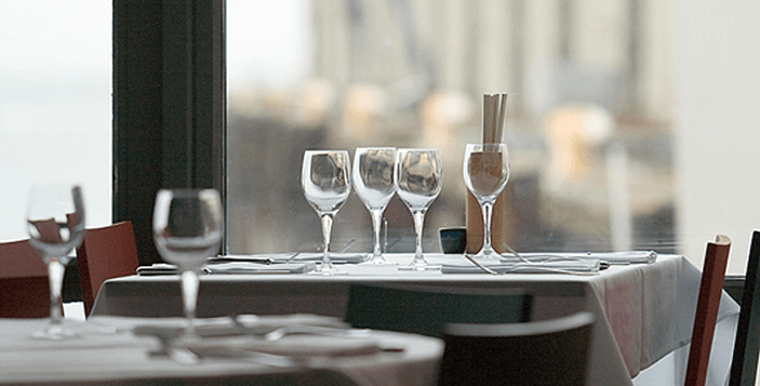 table with white tablecloth, wine glasses, napkins and silverware set ready for diners