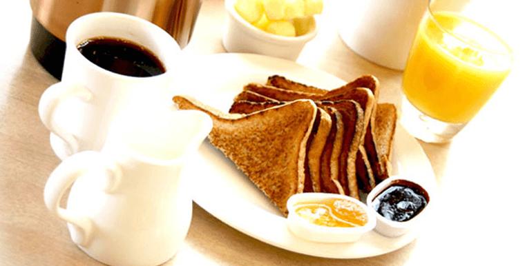Breakfast setting with toast, jam, coffee and orange juice