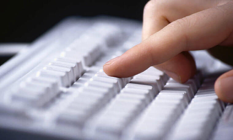 Finger pressing a key on a white computer keyboard