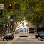 City street shrouded in trees with a light raid train traveling among the cars and buses