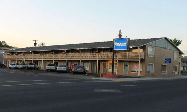 Rodeway Inn & Suites as seen from the road. Beige two story building with gray roof