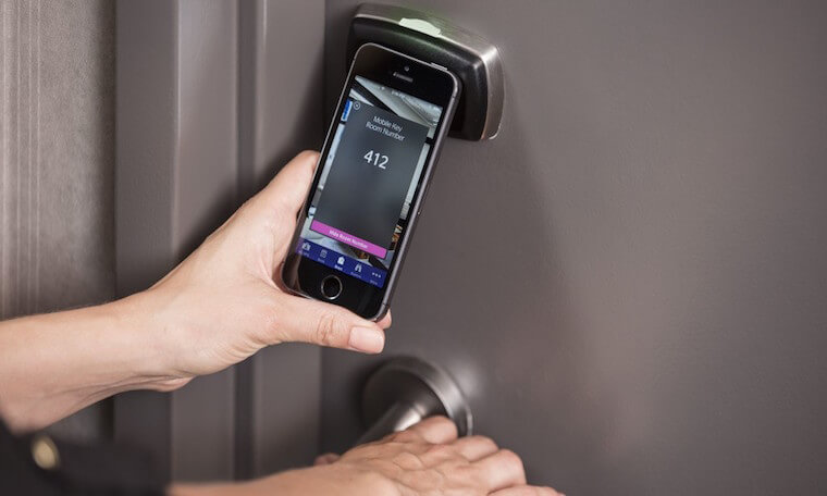 Person using their smart phone to open their room door