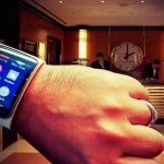Close up of a man with a wristwatch phone in a hotel lobby