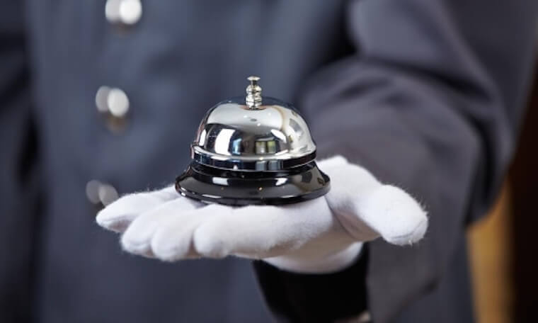 Close up of a person in a blue-grey hotel uniform with white gloved hand holding a ring for service bell