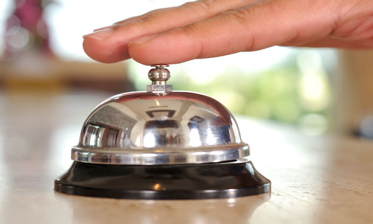 Close shot of a finger ringing a service bell
