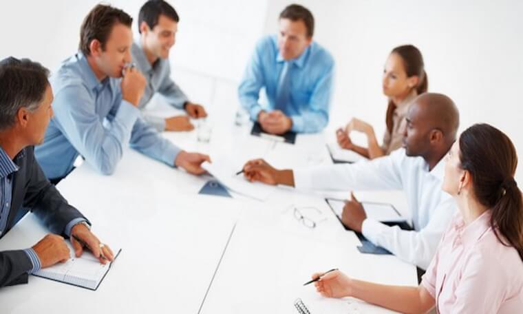Diverse group of white collar workers sitting around a conference table