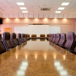 Brown boardroom table lined with chairs
