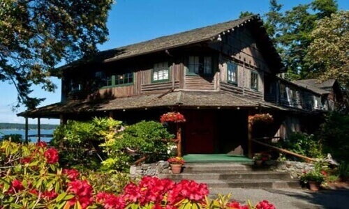 rustic log cabin style 2 story inn with red flowers out front and water nearby behind the inn