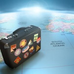Suitcase with many travel stickers sitting on a map of the world