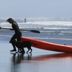 Woman pulling a kayak out of the water onto a beach accompanied by a black labrador